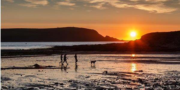 A family walk with their dog along Daymer Bay as the sun sets