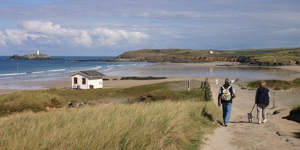 Walkers taking a dog towards Gwithian Towans Beach